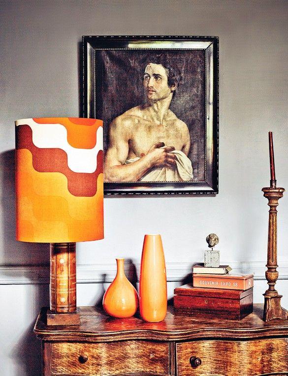 Orange midcentury pieces atop a wooden dresser.