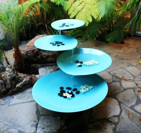 Simple Zen-style garden fountain made from ceramic plates angled just so, and small stones. Even though this one is very high-priced (as seen at link), I am thinking the creative DIY'er could re-create this. http://www.inmod.com/falling-water-fountain.html