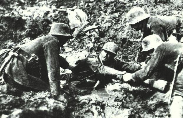 Pendant la bataille autour de Verdun en 1916, trois soldats allemands aident un Français hors de la boue sans fond.