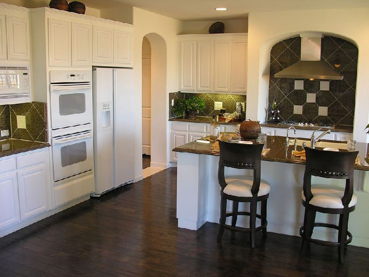 Kuchnia z meblami w kolorze ecru, ciemną orzechową podłoga i hebanowymi krzesłami