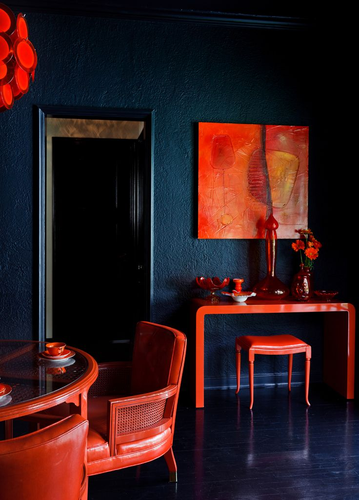 Dark grasscloth walls with red accent furniture and glossy floors.