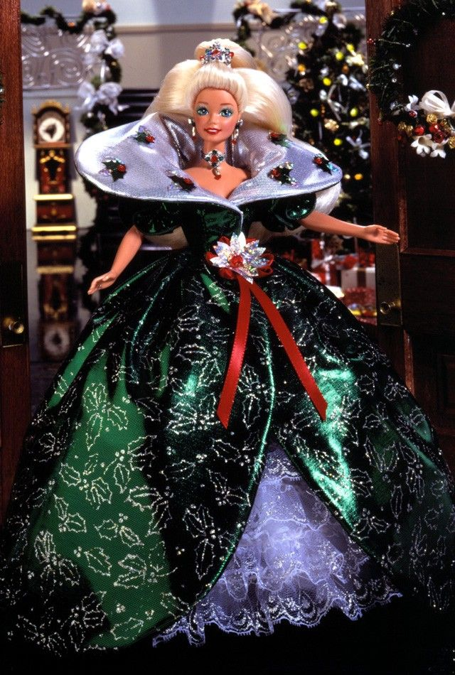 1995 Happy Holidays® Barbie® Doll | Barbie Collector Barbie® doll wants to wish you happy holidays! In a very festive green holly-printed dress with a silvery Victorian collar, Barbie® personifies the charm of the season. Her ensemble is accented by red rhinestone berries, a poinsettia sash, jeweled choker and a red poinsettia in her hair.