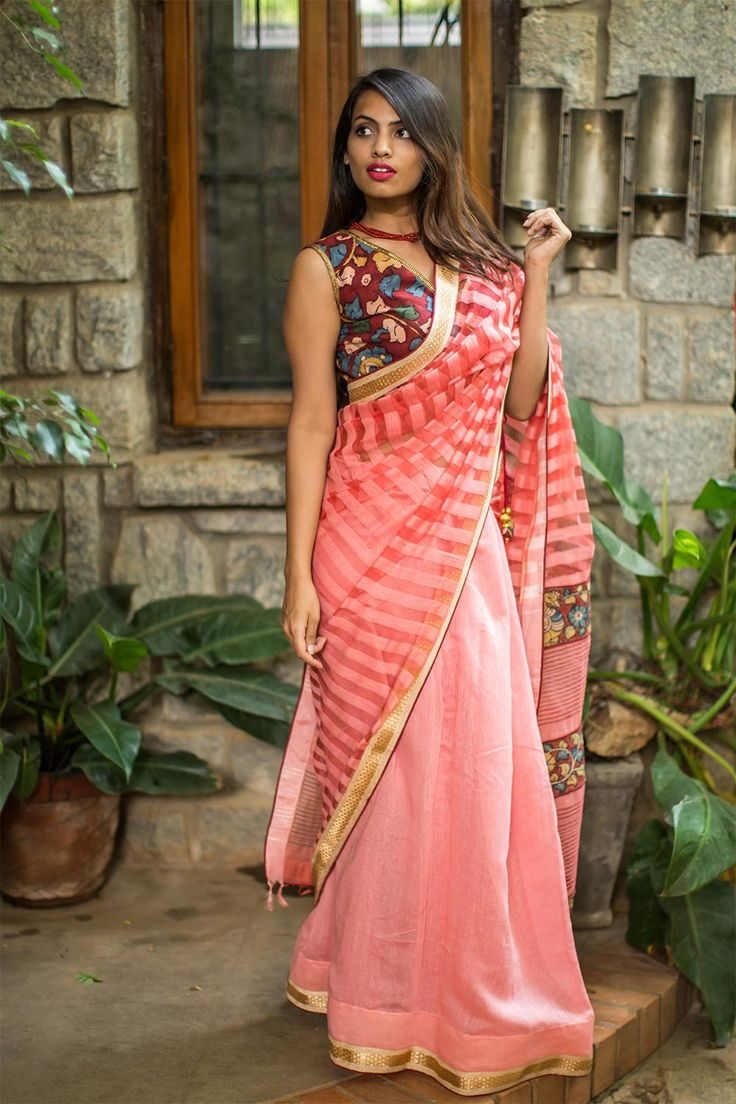 A beautiful cotton silk organza half and half drape in peachish pink color. Sheer striped pallu half with Kalamkari pallu detailing. A true connoisseurs dream this!A maroon Kalamkari blouse pairing would be our top pick! Or go for a more neutral look in a peach pink blouse. #kalamkari #saree #india #blouse #houseofblouse