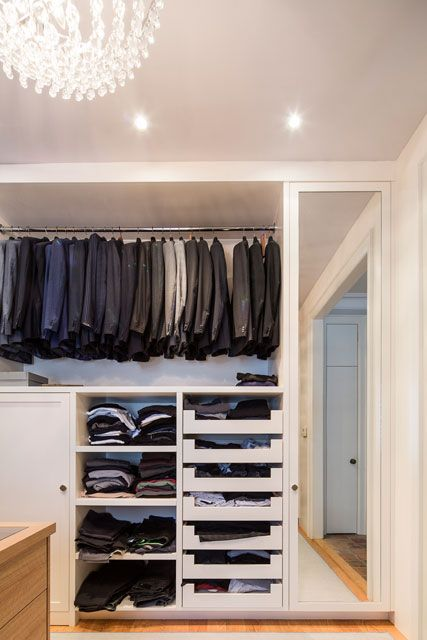 Custom made walk in closet tailored to clients needs and lifestyle. White oak peninsula with felt jewelry inserts and tempered glass top. The double hanging system, continues beyond the white oak front panel. Side luggage storage door pockets in.