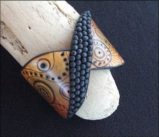 """This cuff by Christelle is titled """"Dreamtime"""". She made this piece for the Australian polymer clay guild's competition """"Australia Speaks"""" and her inspiration came from the symbols and patterns of Aboriginal artwork"""