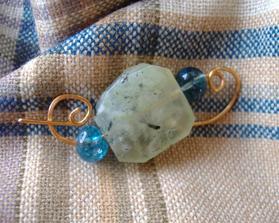 Hammered bronze fibula with faceted Prehnite by CalicoRoseStudio on Etsy.  £10.50.  Soft green genuine gemstone irregular faceted slab, with a translucent blue quartz at either end.  Great for shawls or infinity scarves.