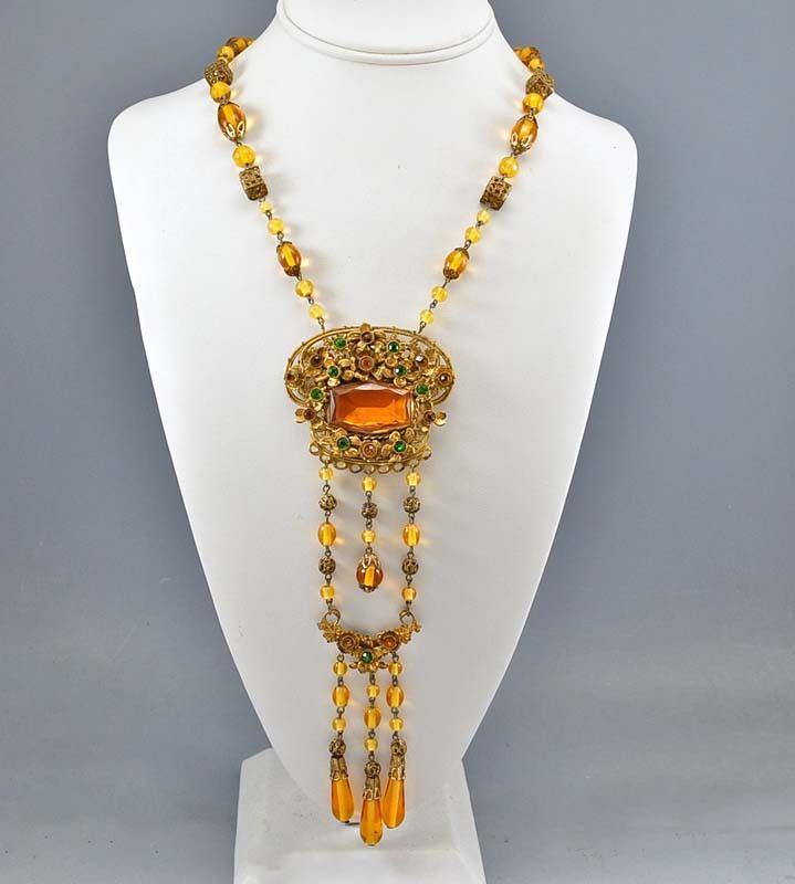 Long superb Czech Art Deco necklace, circa 1920, with delicious honey amber glass. A double drop large gold gilt pendant is centered with an open back faceted amber topaz glass stone with gold gilt fl