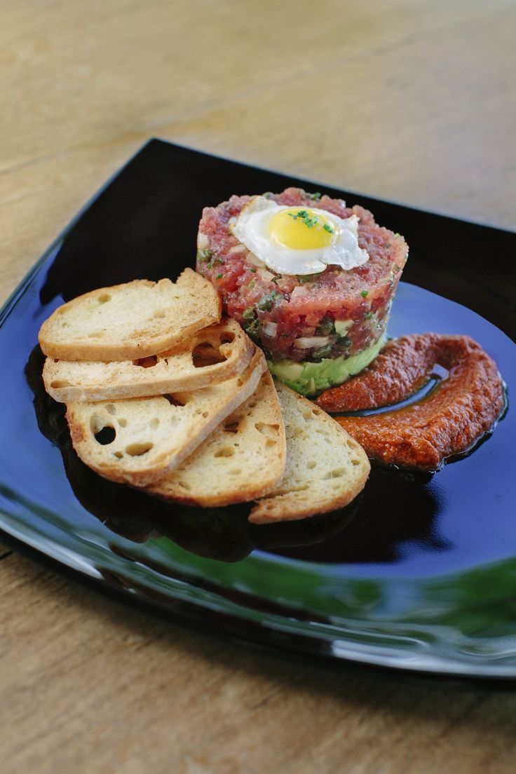 Island Ahi Tartare Tiki Stack-----Minced island-caught ahi mixed with Kula onions & capers, layered with avocado & topped with a sunny side up quail egg. Served with garlic crostinis & a Hawaiian chili harissa swipe. #FoodHeaven #TikisGrill
