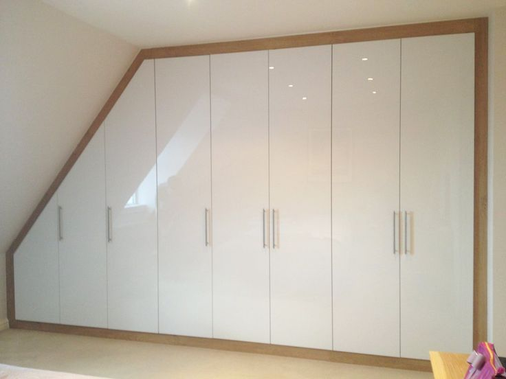 Built-in loft wardrobe with acrylic white gloss doors and oak frame