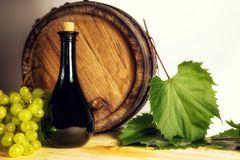 Botella de vino, barril de madera y uvas blancas Fotos de archivo