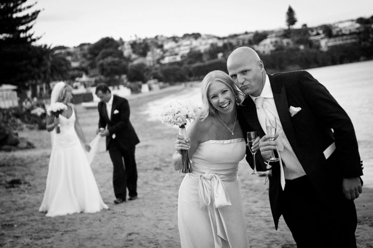 Bridesmaid and groomsman at a wedding at home at Milford beach, Auckland. Black and White.  beguiling fine art family photographs for the walls of the most discerning clients homes. We specialise in wedding and family portrait photography, and supply prints on the highest quality media, framed in beautiful conservation standard frames. We are a high end studio located in the beautiful city of Auckland, New Zealand.