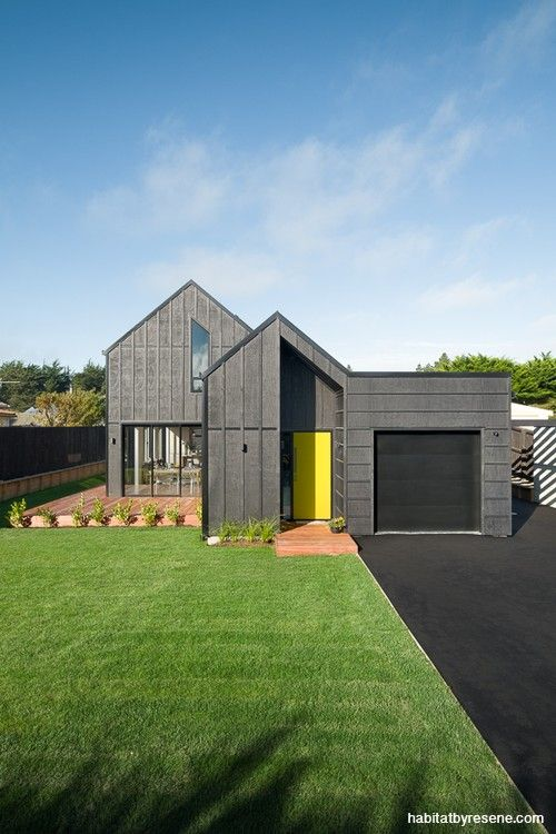 It's hard to miss this modern beauty, finished in Resene Pitch Black wood stain, with a pop of Resene Lemon Ginger on the front door. Project by Barry Connor Design.  Builder Gareth Davis Builders.  Photo by Dennis Radermacher.