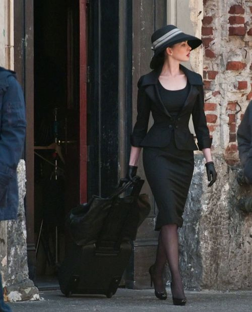 Anne Hathaway as Selina Kyle, wearing a beautifully tailored suit and hat