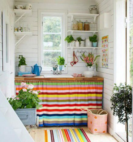 Cutest Tiny Kitchen... <3 colorful striped sink skirt and rug in a white cottage kitchen