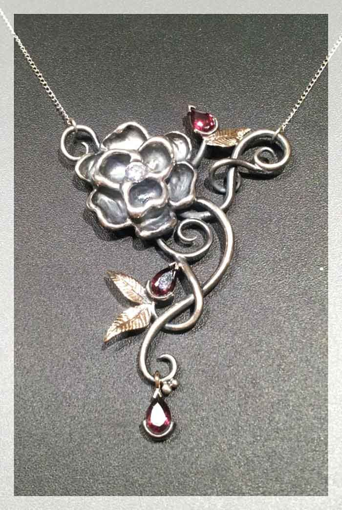 Adorned by Sally Sterling silver and yellow gold necklace. It is set with pear shape garnets.