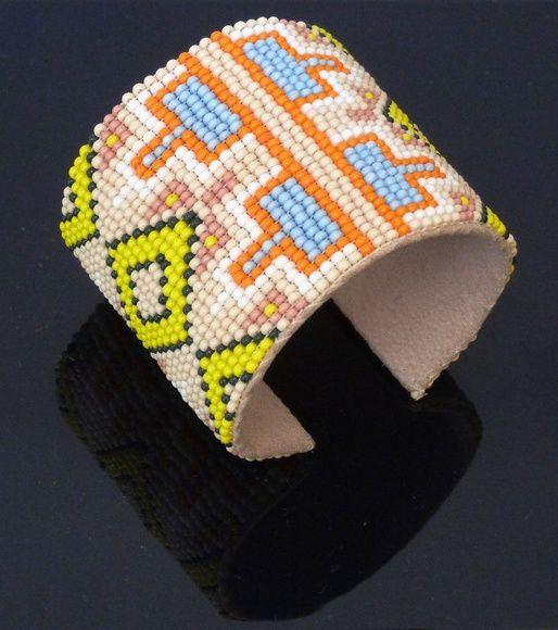Pulseira étnica confeccionada no tear com miçangas encapada com couro costurado, flexível. molda no braço de qualquer espessura.