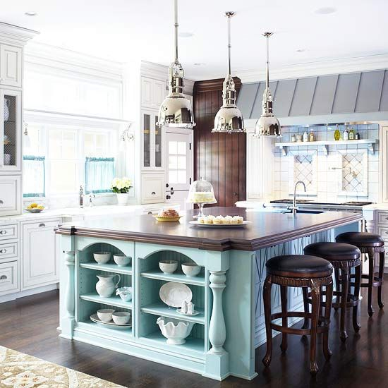 Robin's-Egg Blue A large furniture-style island cloaked in soft robin's-egg blue welcomes family and guests into an impressively detailed kitchen. Crisp white cabinets, a zinc range hood, and gleaming chrome pendant lights pop against the blue island, providing a light and bright atmosphere. Picking up the color of an accent island in accessories adds polish and completes the look.