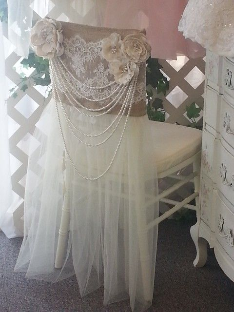 "This vintage inspired chair cover is a very popular rental for Brides that are hosting their reception at a vineyard, barn or other ""outdoorsy"" venue. It evokes a feeling of country romance but yet has a dramatic flair with the long multi-strand pearls. It is a striking and unique rental. The Groom's chair cover is the matching burlap and alencon lace. A Beautiful Touch has dozens of other one-of-a-kind chair cover rentals to choose from!"