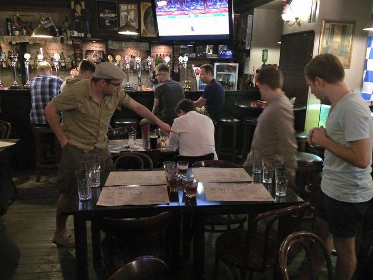 """На этом фото гости нашего паба играют в beer-понг. К вашим услугам в наших пабах множество и других нескучных, как бы спортивных дисциплин: вискибол, марафон по линейке наших британских элей, фехтование на шпажках, которыми скрепляются бургеры; дартс """"после третьей пинты"""" и синхронное плавание по направлению к барной стойке.  Приходите ставить рекорды!"""