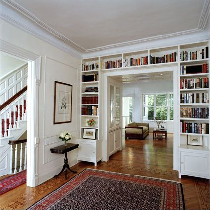 Awesome idea for storing books and giving walls some color without artwork or paint, and I like the little curio built-in hidden in the passageway