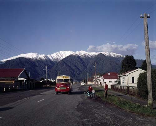 School bus, Whataroa, 1960s. Southern Alps, covered in snow, in the background.