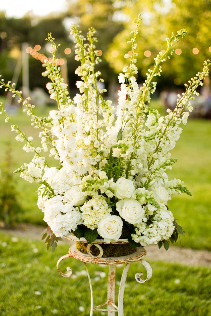 Large floral arrangement: delphinium, white roses and hydrangea in antique stand