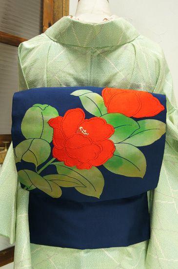 瑠璃のような深い青の地に、つややかな緑の葉と、ふっくらとした赤い花びら美しい花枝模様が織り出された名古屋帯です。