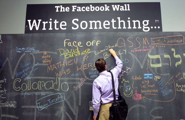 An employee writes a note on the message board at the new headquarters of Facebook in Menlo Park, California January 11, 2012.  REUTERS/Robert Galbraith
