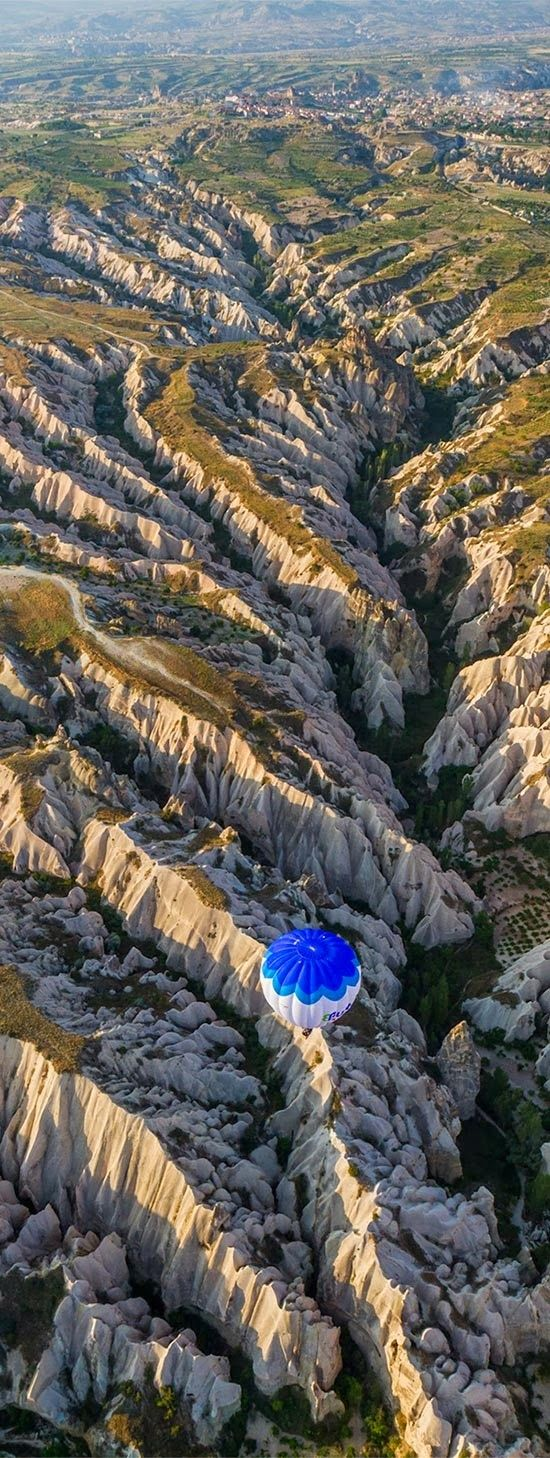 Balloon flying over eroded landscape, Cappadocia, Turkey