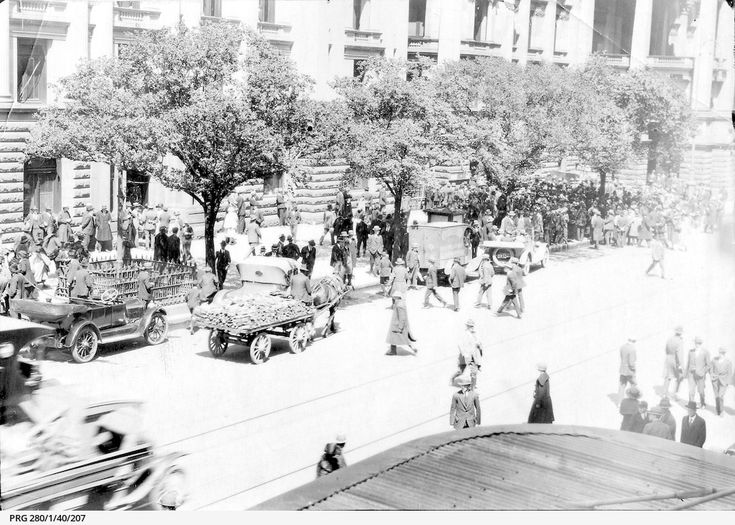 A busy street scene on Swanston Street, Melbourne. Pedestrians mingle with horse drawn carts and motor vehicles, with the Melbourne Town Hall in tha background.