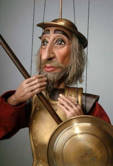 """Don Quixote de La Mancha, Czech-made marionette puppet, 17"""".  The puppet skeleton is hand carved wood. His head and hands are sculpted from a unique plaster compound.  Don Quixote's faithful lance, shield, sword and helmet are all cast in a tin-brass alloy and designed after period models - made by a master bell maker in Prague.  $109"""