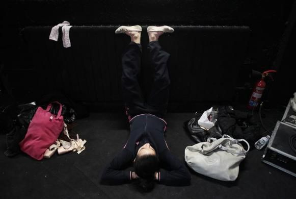 A dancer stretches her feet as she waits for her turn to dance during an audition for 'The Red Shoes' production of Ballet Madrid in Madrid ...