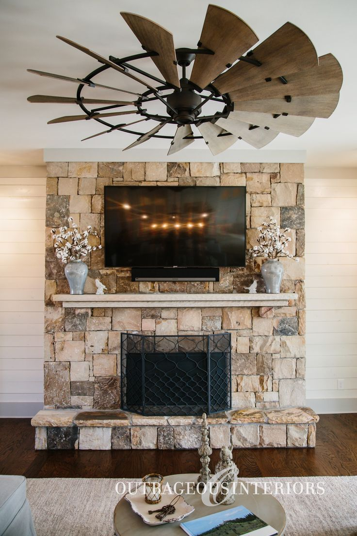 This industrial-style ceiling fan is a great way to complement the fireplace and living room furniture
