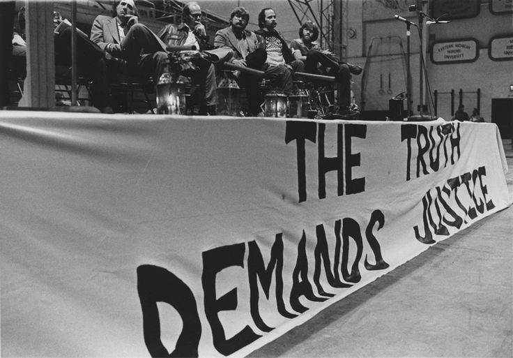"""The truth demands justice"" banner on front of stage, Dean Kahler and others including William Kunstler and Ron Kovic, are seated on stage (seventh annual commemoration)"
