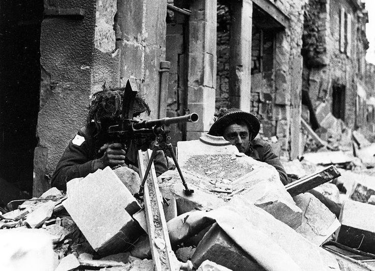 Two Canadian soldiers with a Bren gun in Caen, France, July 1944.
