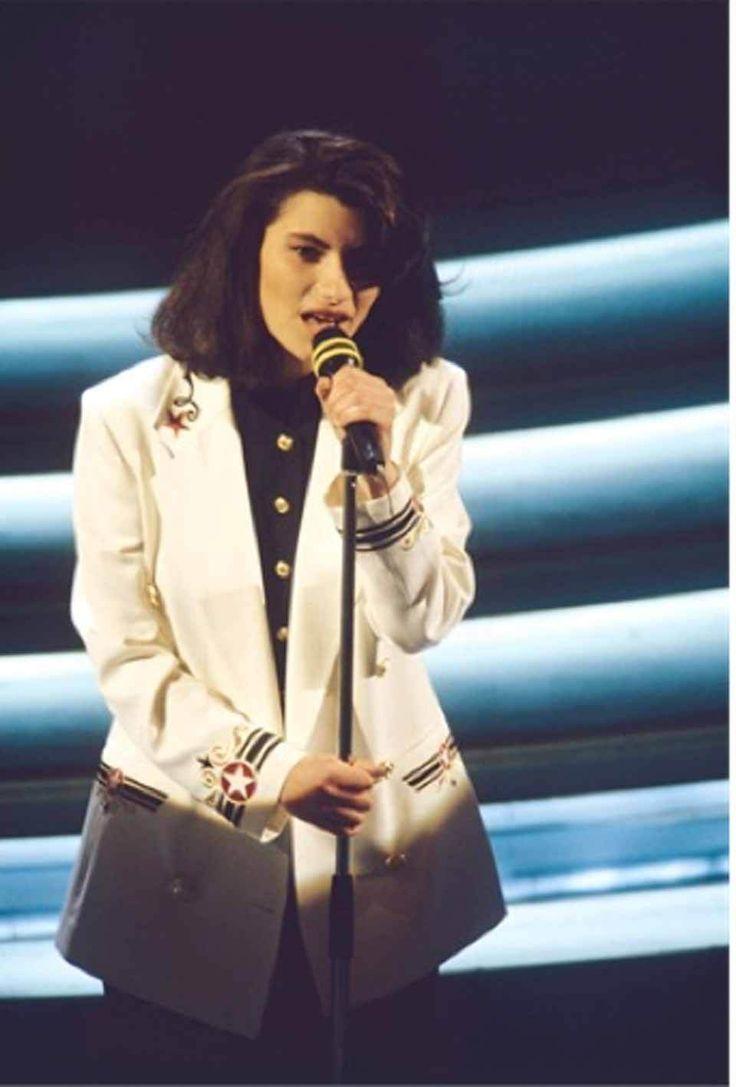 """Sanremo Story, i look peggiori nella storia del festival. Laura Pausini nel 1993 canta """"La Solitudine"""", giacca stile alla marinara. Ha indossato Byblos, Armani e Philippe Plain, ma nel 1993 e nel 1994 ha scelto una serie tailleur troppo austeri e antiquati, non adatti a una giovane ragazza che appariva assai più grande della propria età."""