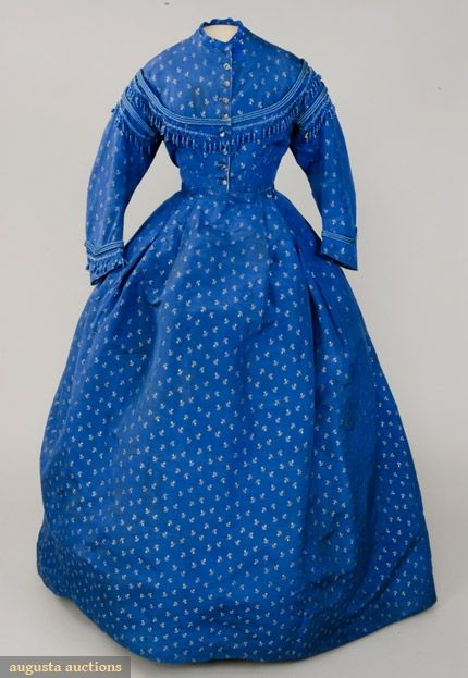Blue Silk Brocade Day Dress, 1860's;  Fine ribbed silk woven with allover white floral sprigs, collarless, eight glass buttons at center front opening, satin cord & silk fringe with clear glass beads, long curved sleeves, full pleated skirt with slight train and center back gathers, cream linen bodice lining.
