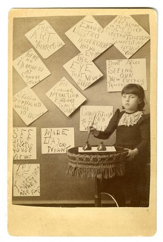 """ca. 1870-1900s, [Advertising Cabinet Card showing girl with brush and ink making signs for the wall: The Art of Perfection,"""" Ennors Electro Tassergraph has no Equal,"""" The Eye that Never Sleeps,"""" etc.], The Famous Bay Window Photograph Gallery via Jeffery Kraus Antique Photographica   From 'Stevens Point, Wisconsin.' Our favorite line: """"Cloudy weather Preferred for Sitting"""":"""
