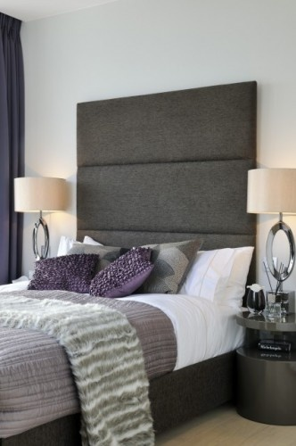 Four rolls of batting, a sheet of 1/4 inch plywood, fabric screws and a stable gun--and this could be yours!  More important is the choice of padded headboard verses hard--your back will thank you.  This hotel effect is cheap and effective.