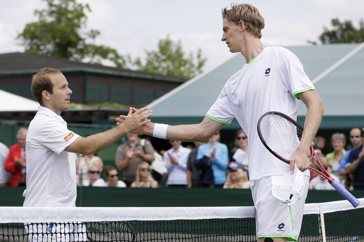 PLAYING HIGH: Kevin Anderson of South Africa, right, shook hands with Olivier Rochus, of Belgium, after Mr. Anderson won their Men's first round singles match at Wimbledon in London Tuesday. (Alastair Grant/Associated Press)