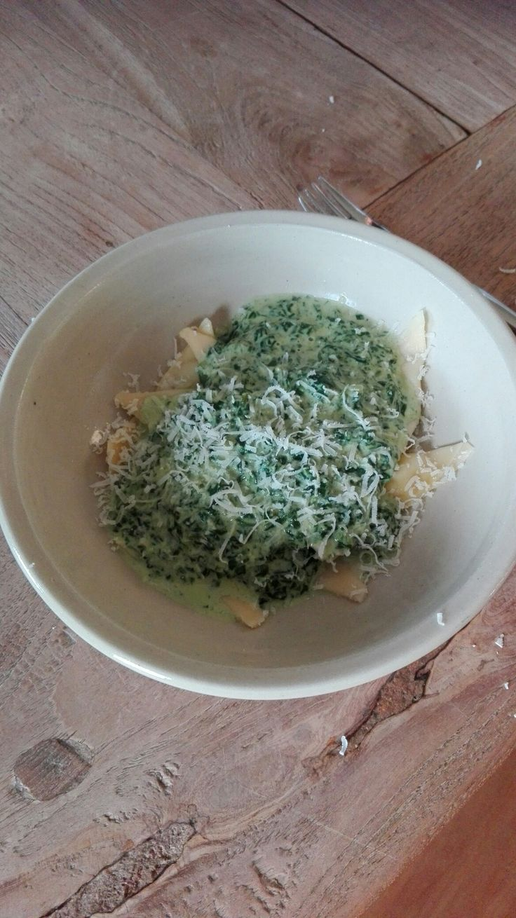 Zelfgemaakte pasta ravioli met vulling van ricotta en gekruide boschampionnen + roomsaus van spinazie + Parmezaanse kaas.