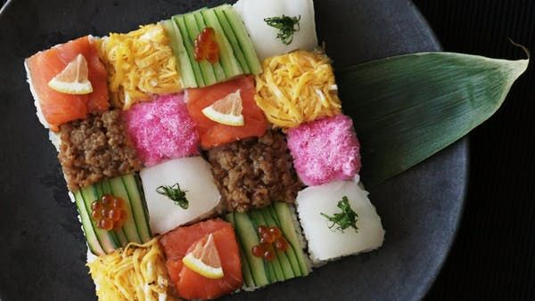 How to make a Mosaic Block Sushi. Ingredients: 280 cc rice, 260 cc water, 4 tsp sake, (sushi rice seasonings), 40 cc rice vinegar, 2 tsp sugar, 1 tsp salt, (sushi fillings and toppings), 3 sheets nori, cut in half, 2 slices smoked salmon, 3 thinly sliced lemon, 1/2 cucumber, thinly sliced, ikura (salmon roe), sakura denbu (pink fish flakes), 1 small fillet of squid (sashimi quality), 1 pirella leaf, cut into thin strips, (seasoned ground chicken), vegetable oil, 50 g ground chicken, 1 tb...