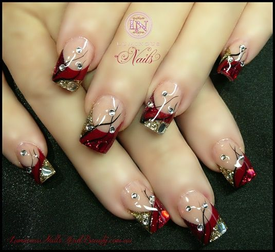 Red and gold Christmas-themed nails.