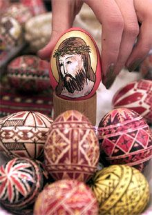 A woman arranges a traditional Orthodox Easter egg painted with the image of Christ