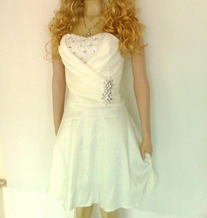Detalle vestido corto en tafetán blanco con pedrería plateada.