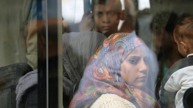 Des réfugiés prennent place dans un bus après leur arrivée à la gare de Munich (Allemagne), le 7 septembre 2015. | CHRISTOF STACHE / AFP