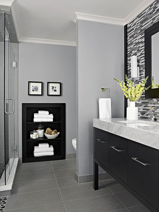 What could have been a wasted wall between the toilet and shower was maximized with a recessed set of shelves, trimmed in the same rich wood as the rest of the bathroom for a coordinated look.
