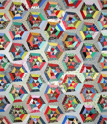 'Sunday Paper' inspired by a Victorian Hexagon Quilt. by Sujata Shah -- this looks like a random string quilt, but all of those seams and points match. It must be paper foundation pieced.
