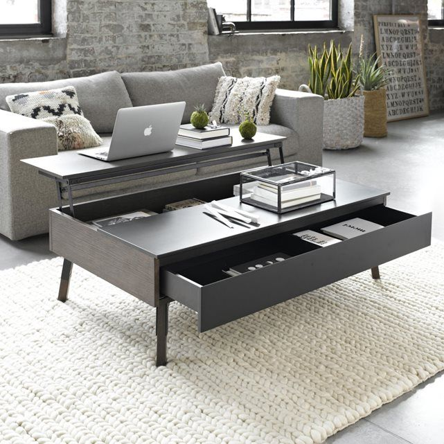 Irma coffee table. This coffee table is decorative and functional all in one! A great space-saving solution too! It features a clever split table top which lifts up to reveal a large storage space underneath and a large drawer. Fold out this table top into the ideal workstation for a laptop.   Features: - In oak-veneered MDF and charcoal stained MDF.  - Solid oak legs with charcoal painted metal bracket.  - Drawer with 2 compartments.   Size:  - L113 x H36 x D79 cm. - Useable drawer…