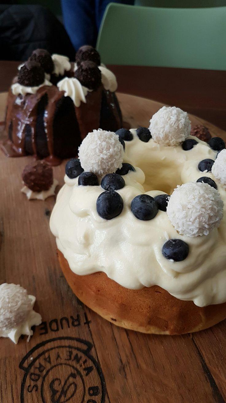 White chocolate mini bundt cake with white chocolate ganache, blue berries & coconut ferrero roche .. in the back is mini chocolate bundy cake with dark chocolate ganache & dark chocolate ferrero roche